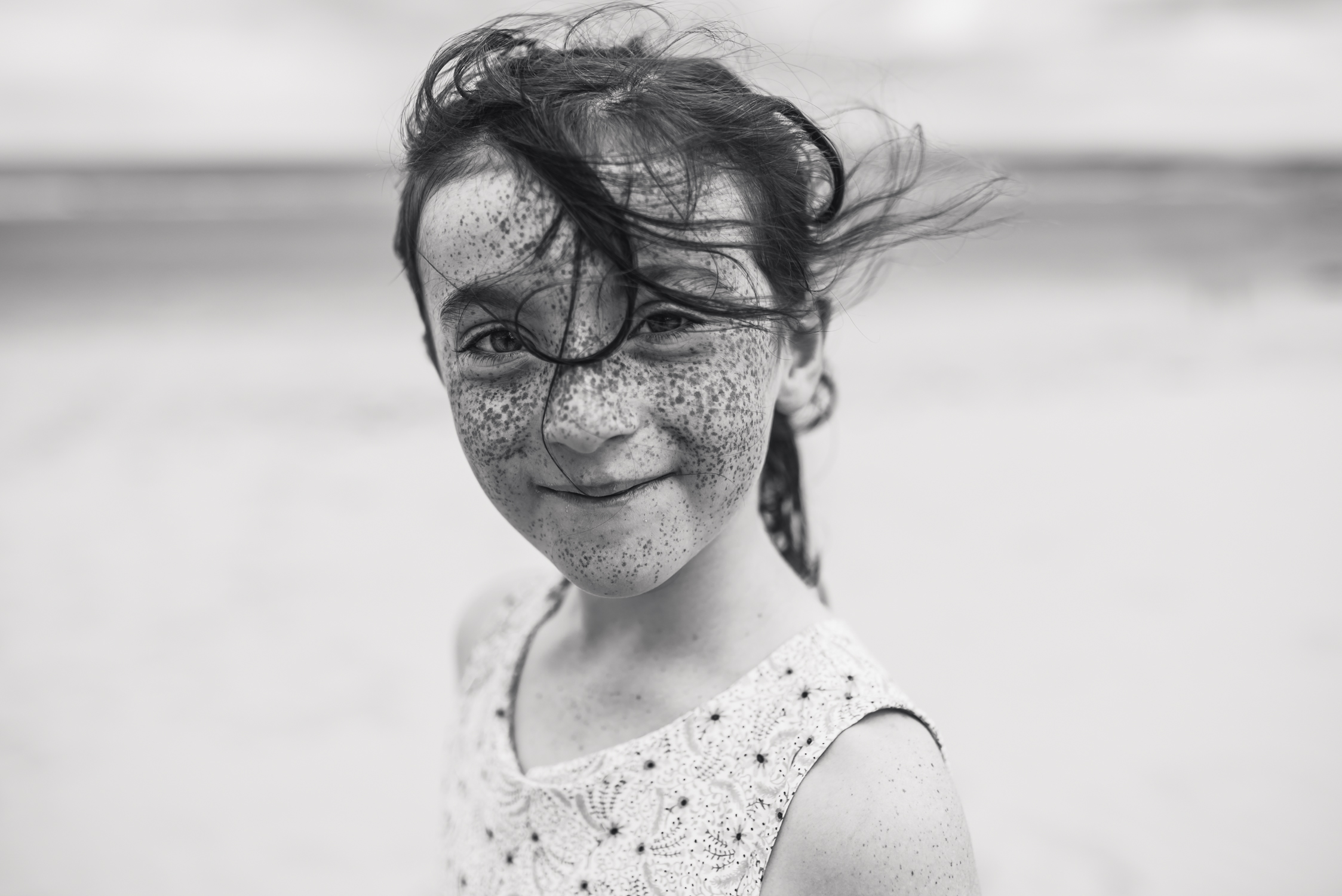 little girl with freckles on beach