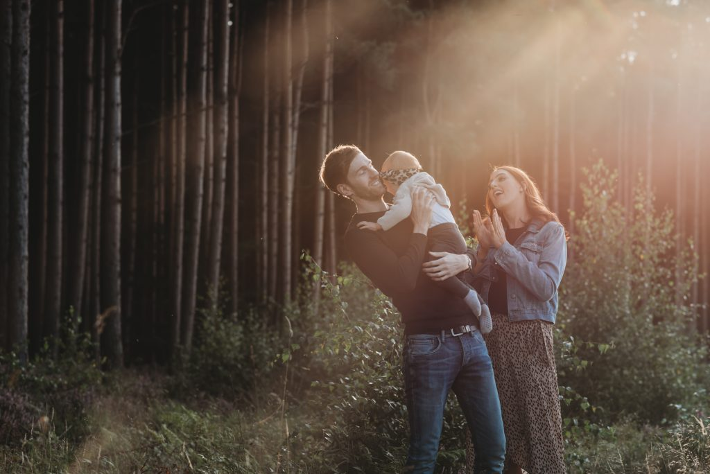 couple with baby in the woods with sunlight shining on them