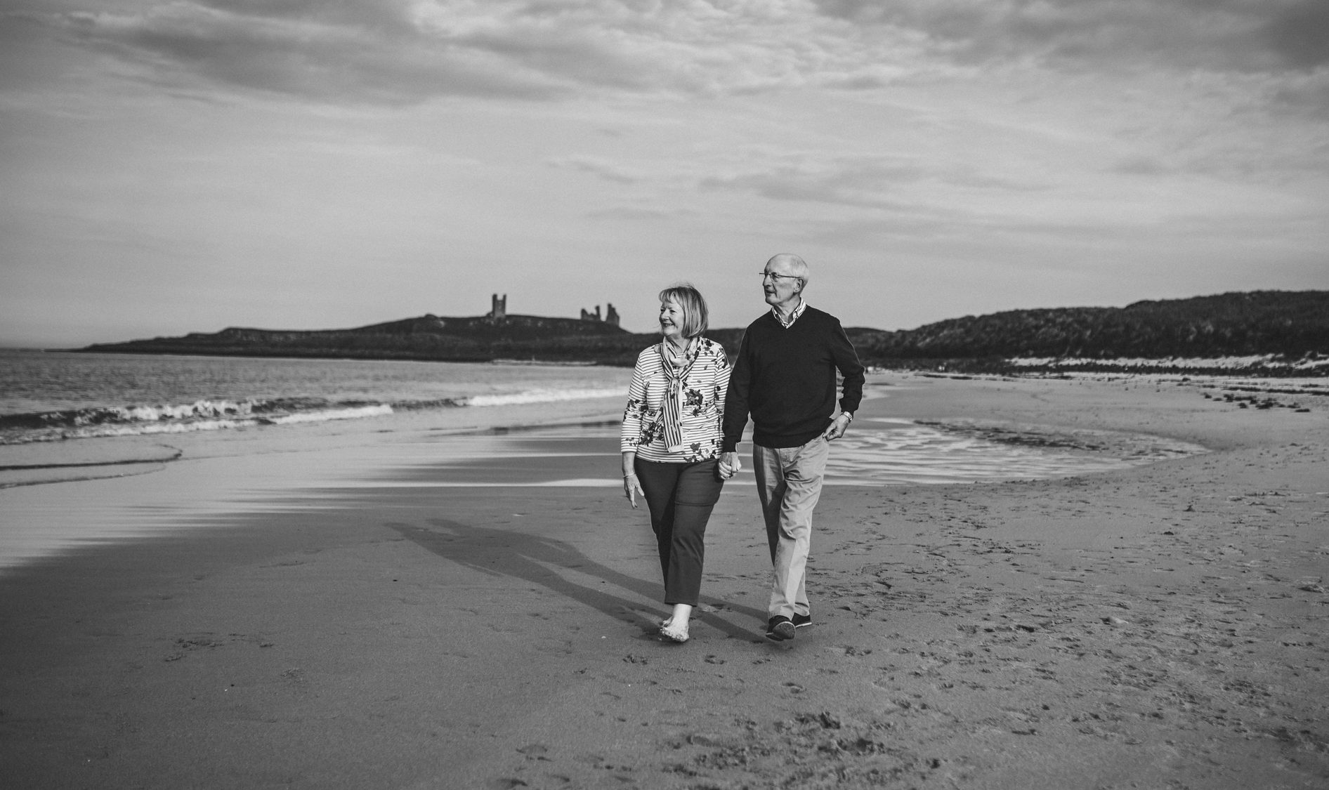 couple walking along the beach with Dunstanburgh castle in background