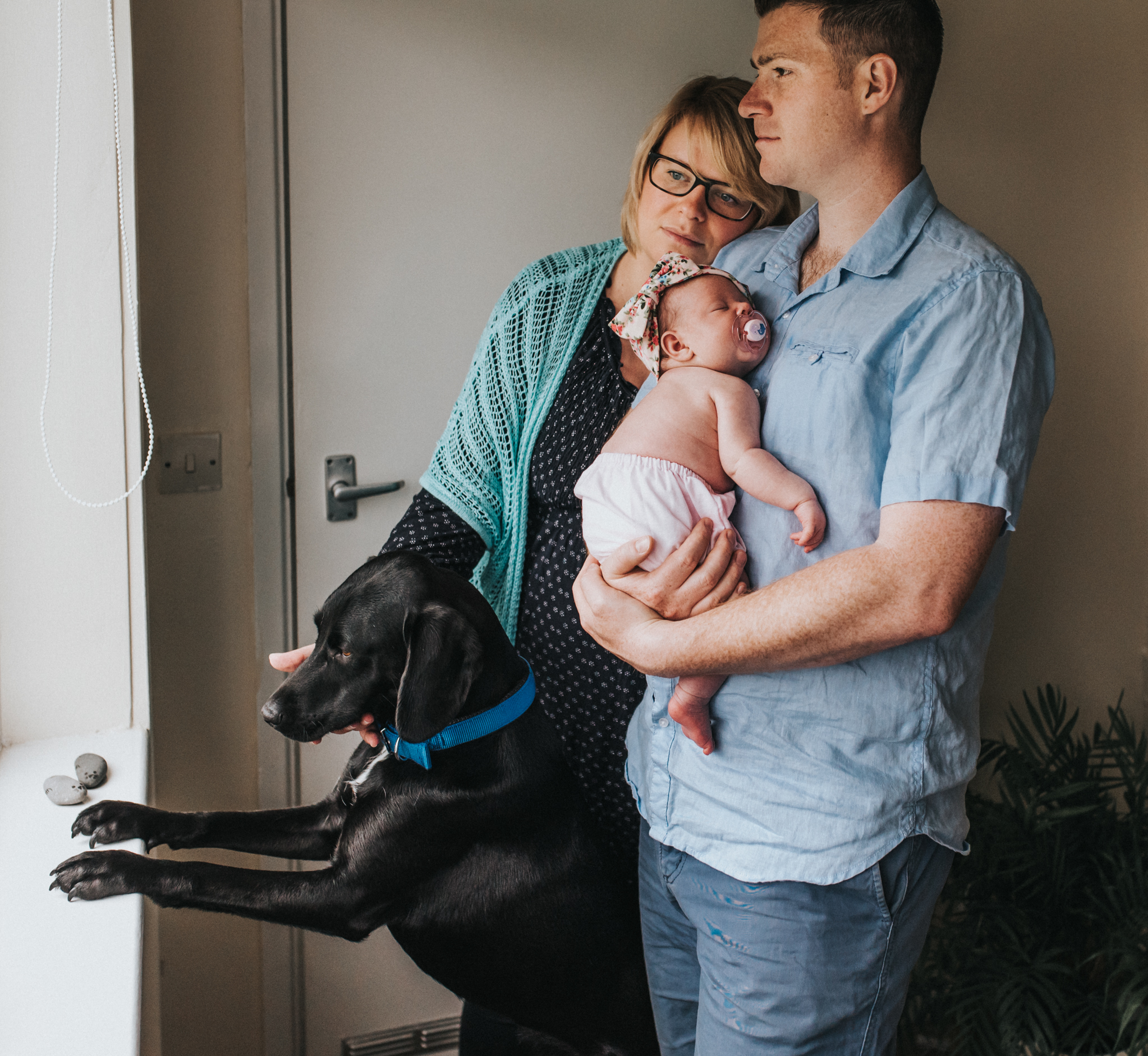 family with dog and newborn looking out of window