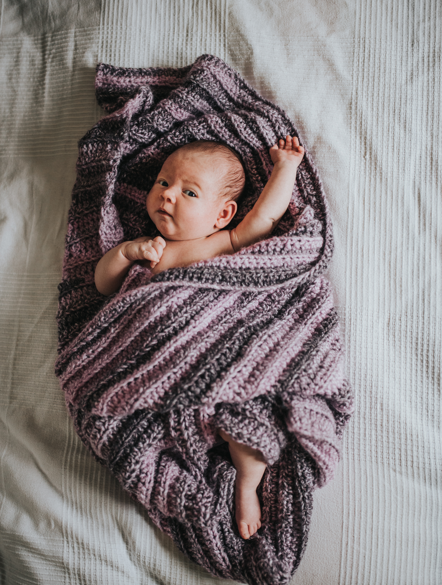 Newborn baby wrapped in blanket on bed