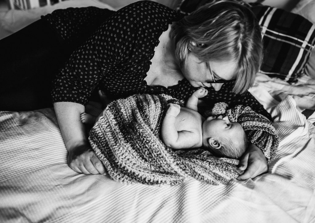mother and newborn baby on bed