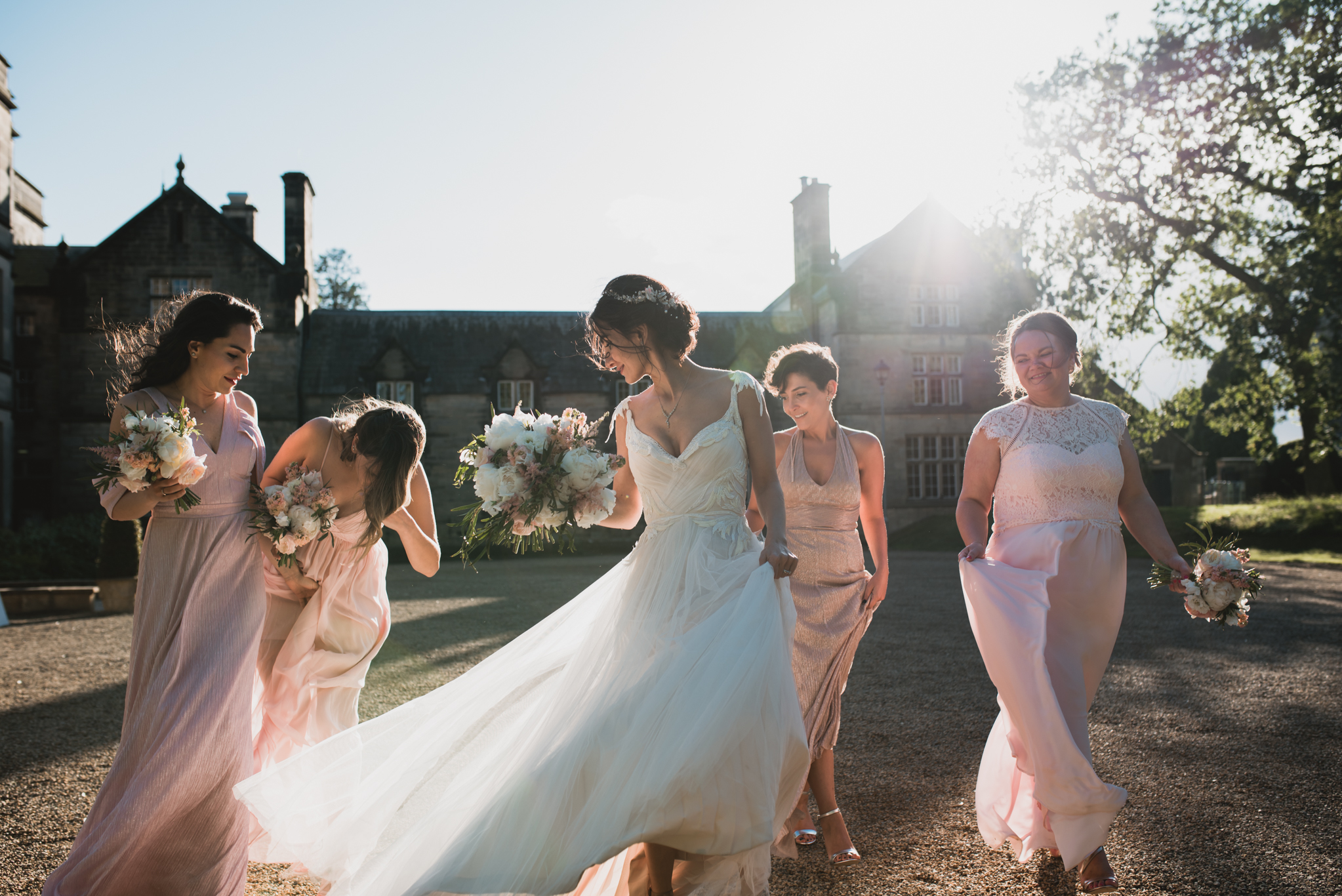 bride and bridesmaids walking in sunlight