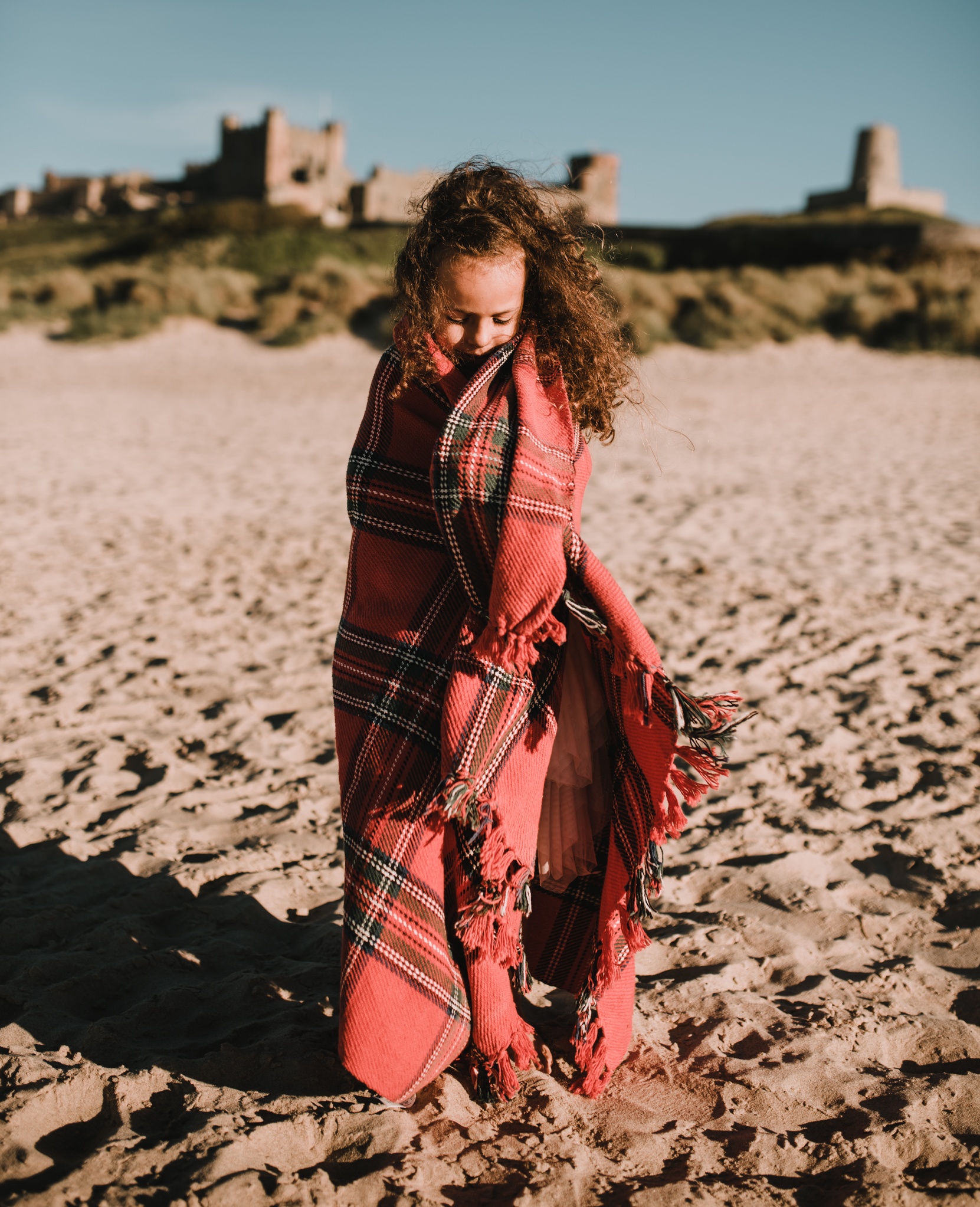 Little girl wrapped in blanket at bamburgh beach