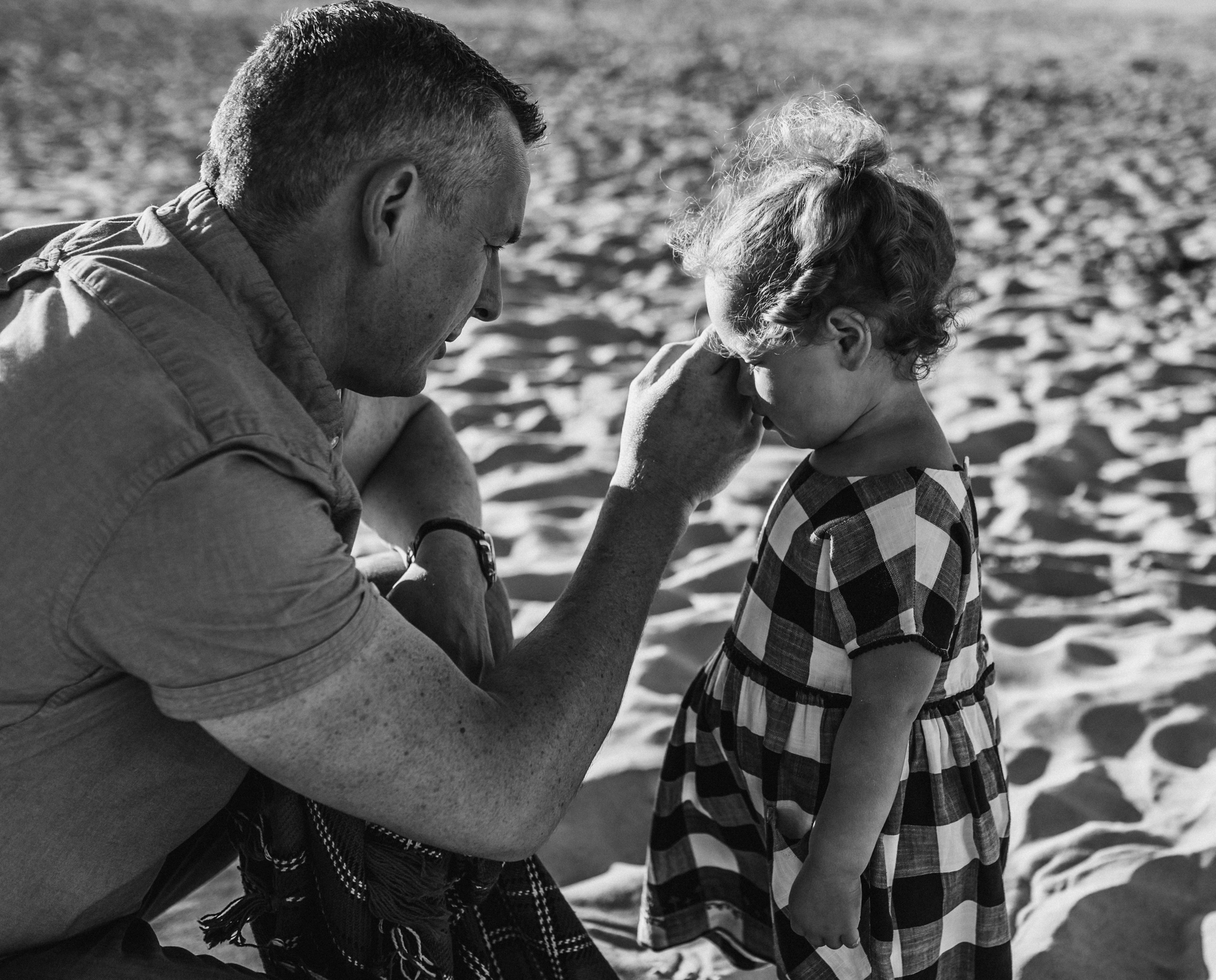 dad wiping little girls tears at the beach