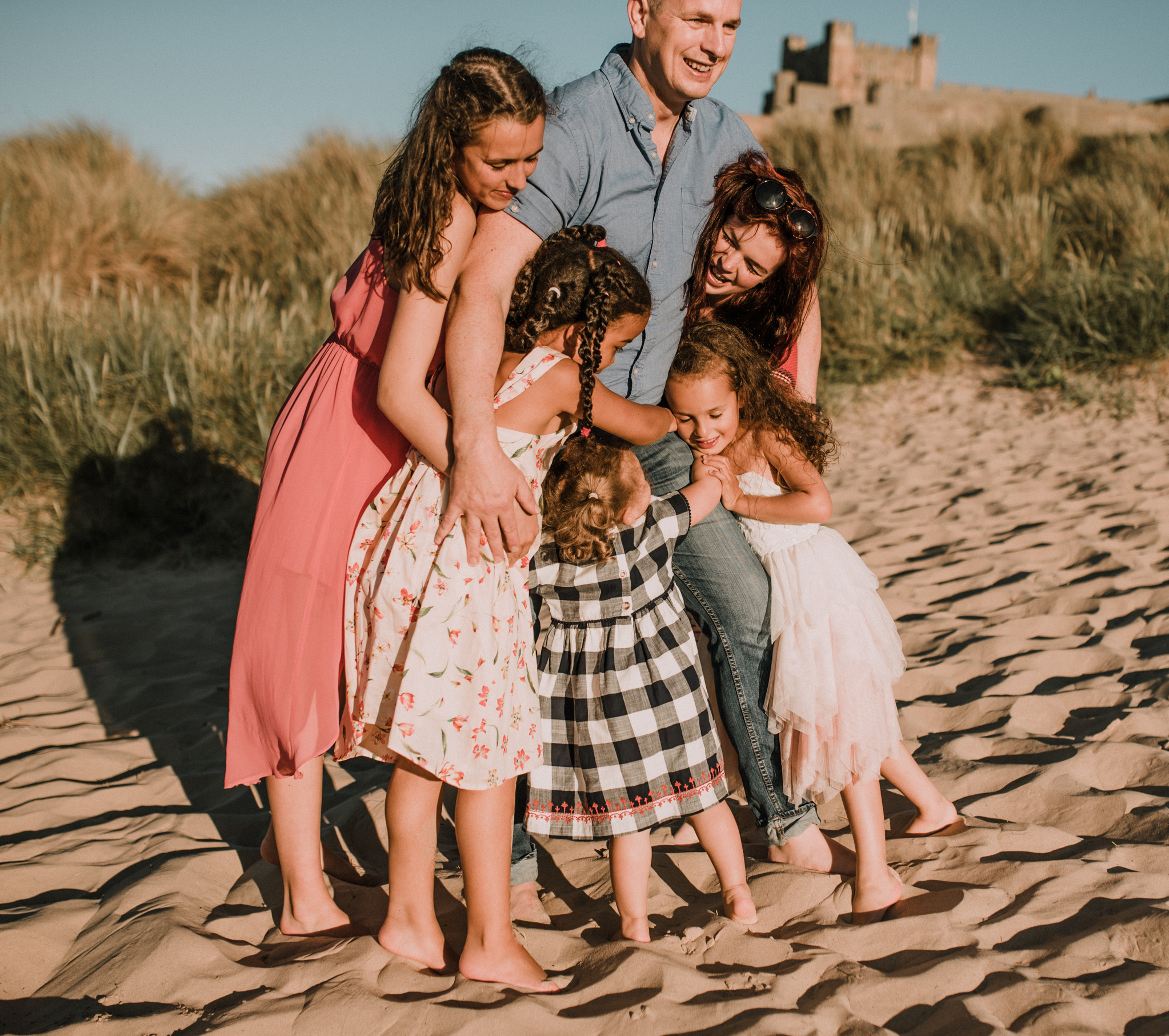 dad with 5 daughters on beach