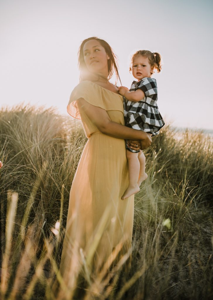 mother and child on beach with sunlight behind them