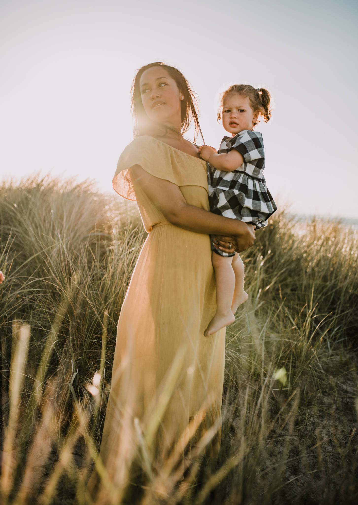 mother and child on beach with sunlight behind them Family photographer north east
