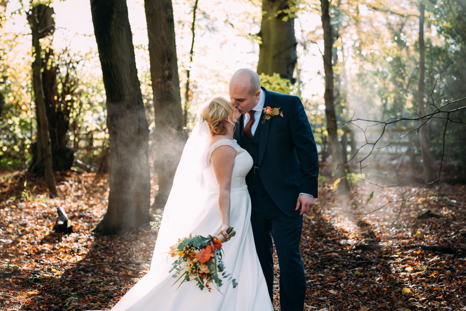 Bride and groom kiss in woods at Shotton Grange Wedding