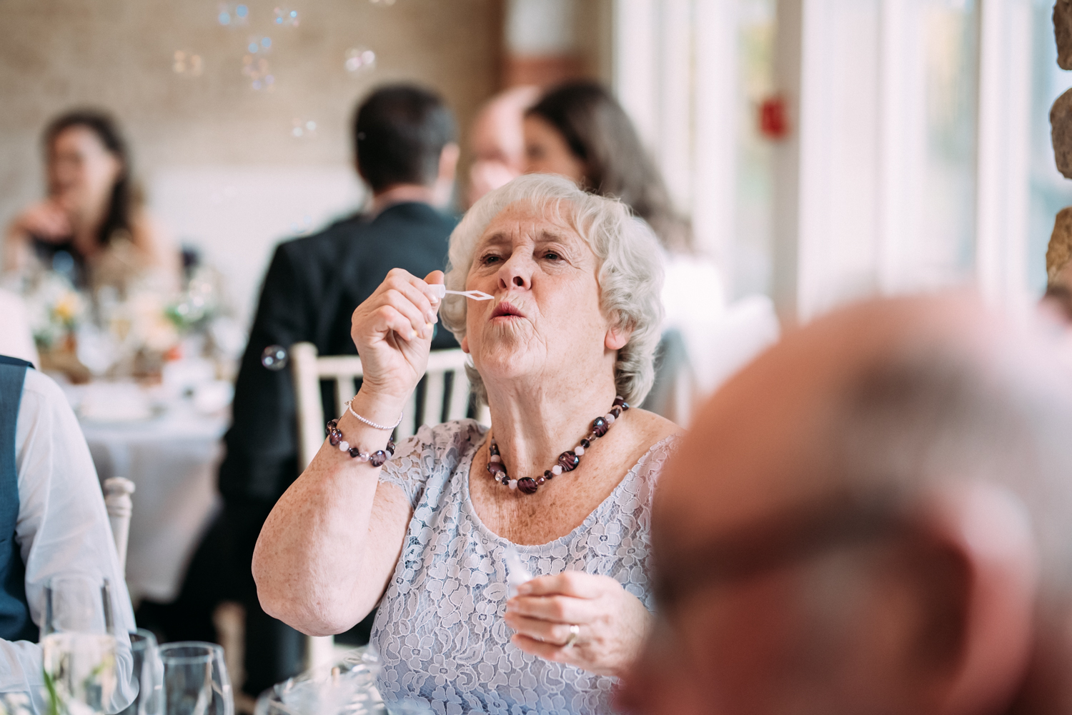 elderly lady blowing bubbles at Shotton Grange Wedding