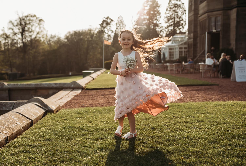 little flower girl twirls around outside at Wedding at Maften Hall