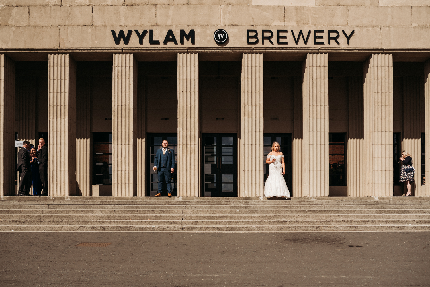bride and groom stand in front of brewery at Wylam Brewery Wedding