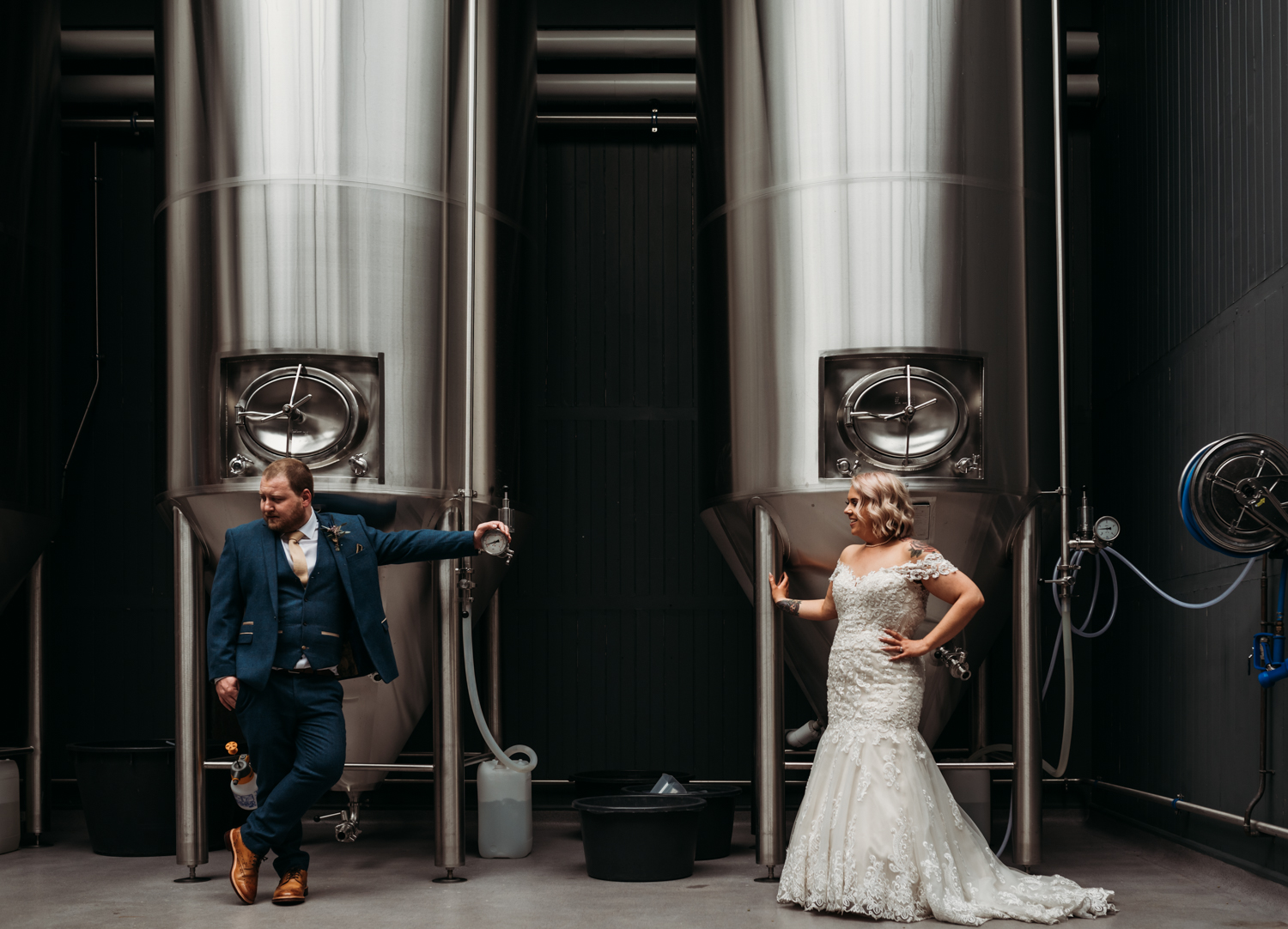 bride and groom pose in brewery at Wylam Brewery Wedding