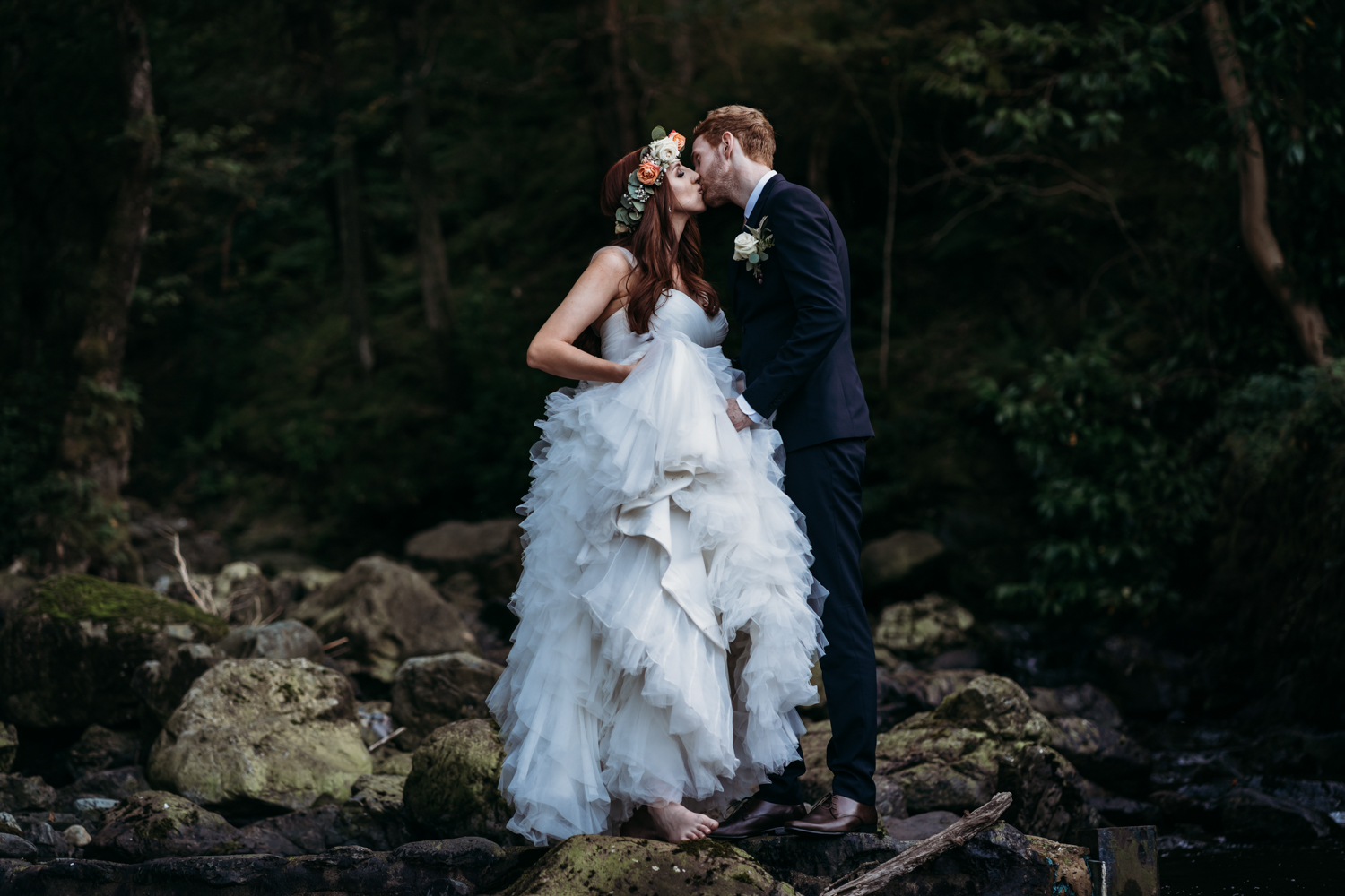 bride and groom kiss on the waterfall rocks at Lodore Falls Wedding