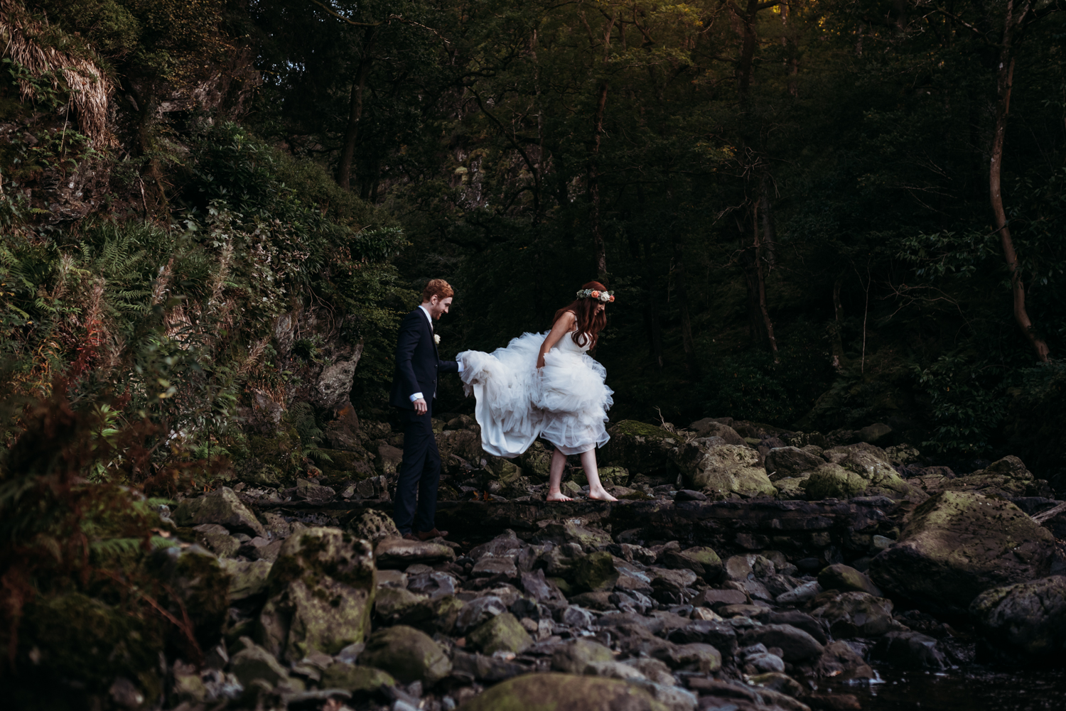bride and groom walk across the waterfall at Lodore Falls Wedding