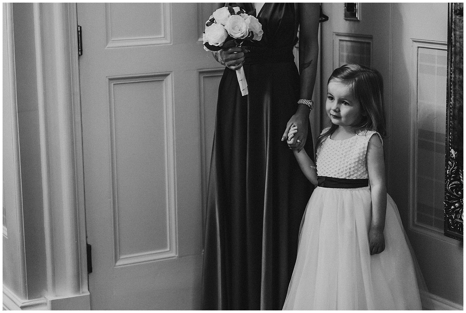 little flower girl looks at bride at auchen castle wedding